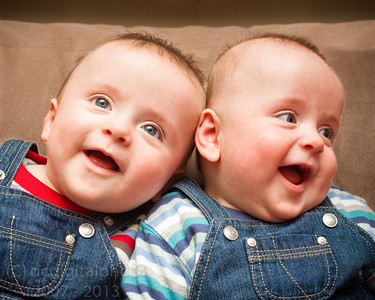 Twin boys in overalls smiling